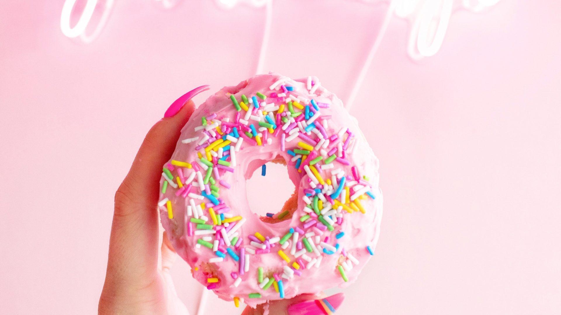 Hand mit pink lackierten Fingernägeln hält Donut mit pinkem Guss und bunten Streuseln. Darüber steht in Neonschrift: You are magic.